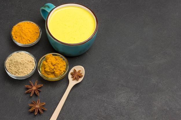 Goldener latte mit zutaten zum kochen von kardamom, zimtstangen, sternanis