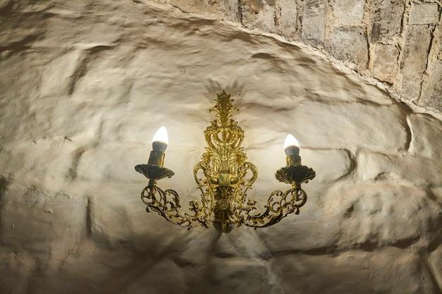 Goldener leuchter mit zwei kerzen an der antiken steinmauer des schlosses. kasan