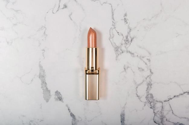 Goldener lippenstift auf weißem marmorhintergrund. flach liegen. draufsicht