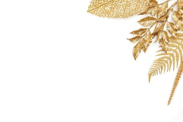 Goldener lorbeer und farnblätter auf weiß. speicherplatz kopieren.