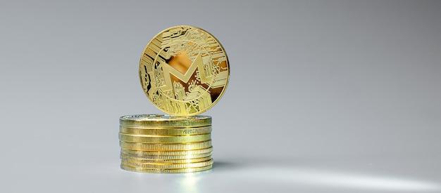 Goldener monero-münzenstapel auf grauem hintergrund