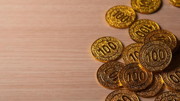 Goldener münzenstapel auf hölzernem qith kopienraum
