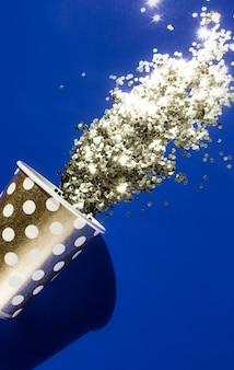 Goldener pappbecher für geburtstagsfeier mit goldenem konfetti auf blauem hintergrund.