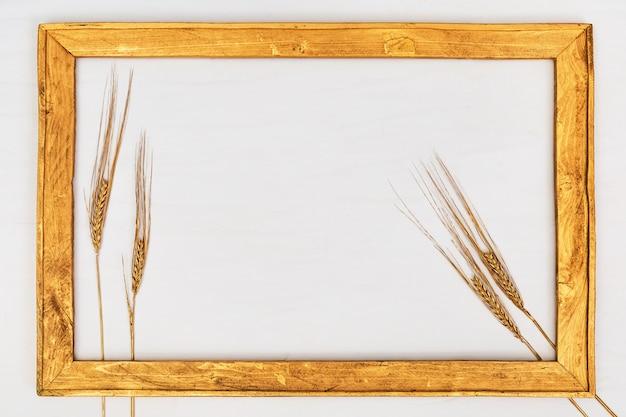 Goldener rahmen der hölzernen weinlese gemacht vom holz mit den ährchen des roggens. von reicher ernte. herbst kreatives stillleben. minimaler arthintergrund mit copyspace.