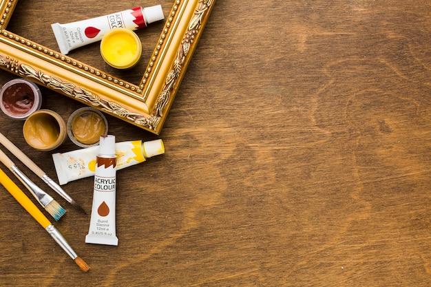 Goldener rahmen mit farbe und pinseln