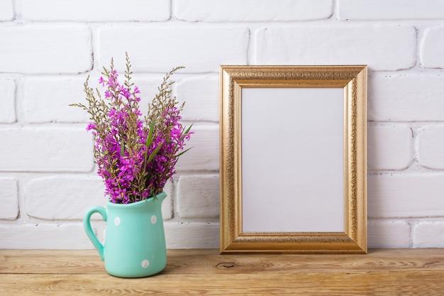 Goldener rahmen mit kastanienbraunen lila blüten im minzkrug