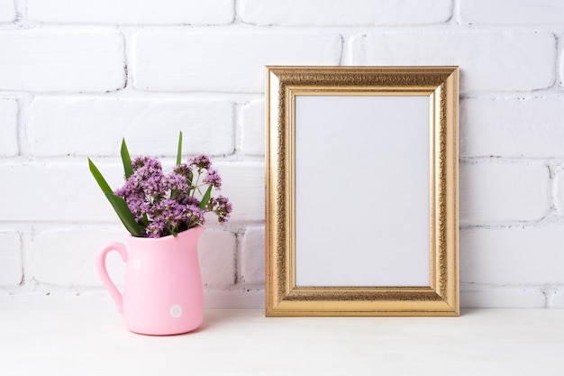 Goldener rahmen mit lila blumen im rosa rustikalen krug
