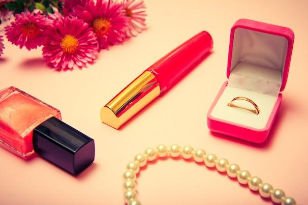 Goldener ring in box, perlen, nagellack, lippenstift und blumen auf rosafarbenem hintergrund. damenschmuck und accessoires. farbe getönt.