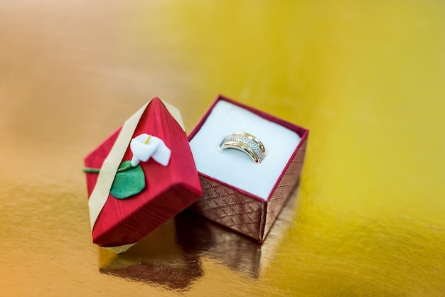 Goldener ring in roter geschenkbox auf goldenem hintergrund