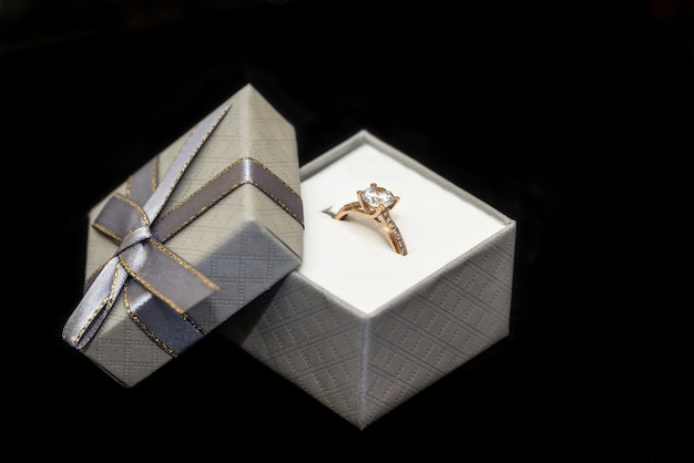 Goldener ring mit diamant im kasten lokalisiert auf schwarz