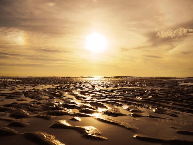Goldener sand plätschert oberflächenmuster auf sonnenuntergangstrand.