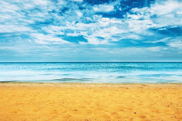 Goldener sandstrand mit blauem ozean und wolkenlandschaft