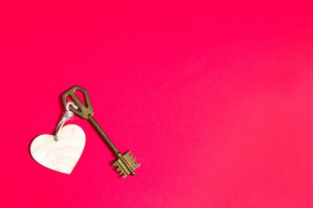 Goldener schlüssel mit holzanhänger in der form eines herzens auf einem roten hintergrund