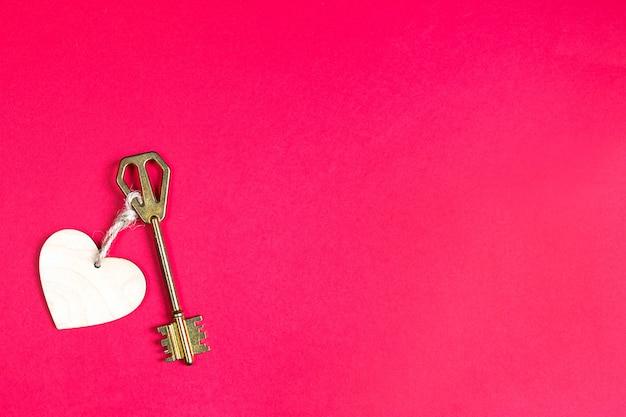 Goldener schlüssel mit holzanhänger in der form eines herzens auf einem roten hintergrund Premium Fotos