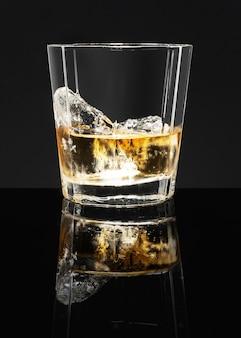 Goldener scotch whisky auf einem schwarzen hintergrund