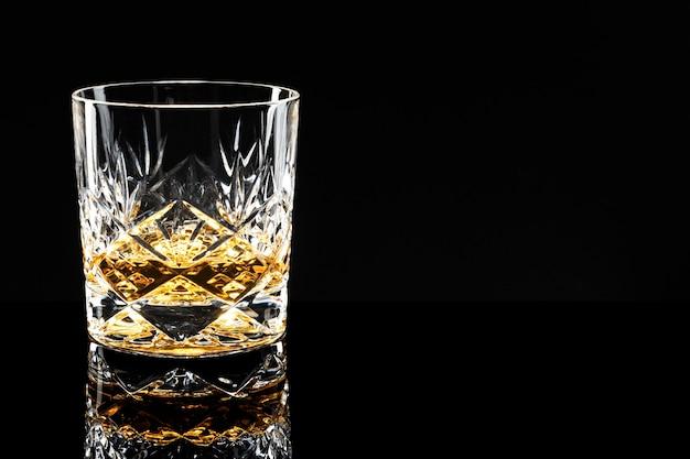 Goldener scotch whisky auf schwarzem hintergrund