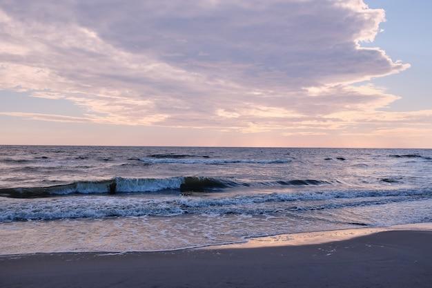 Goldener sonnenaufgang hinter den wolken, rosa himmel und ruhigem see. seelandschaft am abend