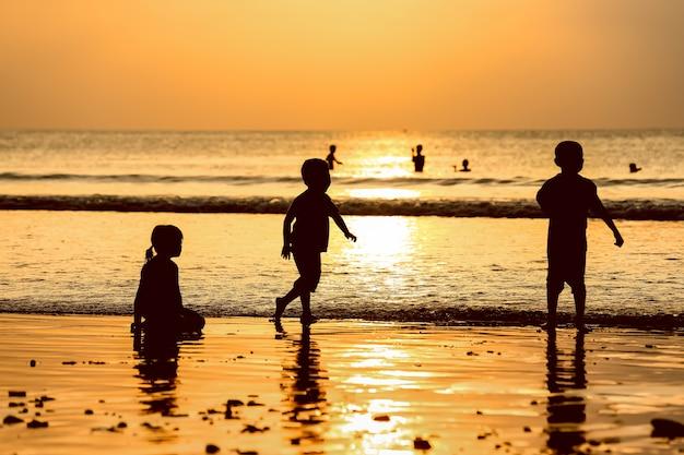 Goldener sonnenuntergang und kinder genießen, auf dem strand mit sonnenstrahlenhimmel zu spielen