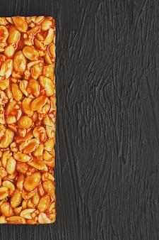 Goldener steinpilz kozinaki von den gebratenen erdnussbohnen-energieriegeln. schwarzer struktureller hintergrund, draufsicht