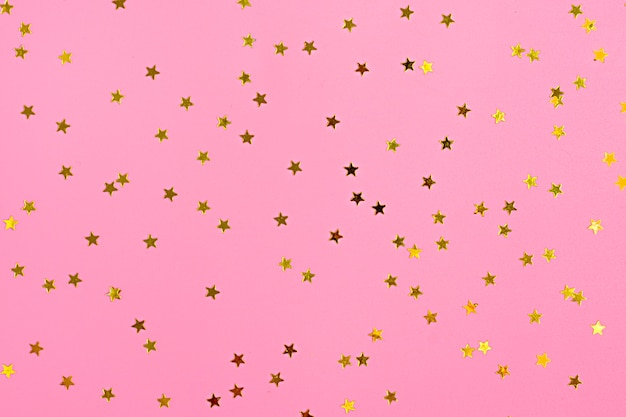Goldener stern besprüht auf rosa. festlicher feiertagshintergrund. feier-konzept. draufsicht,