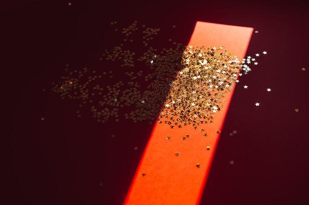 Goldener stern confetti im harten licht mit schatten
