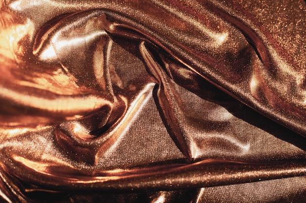 Goldener stoff in wellen, texturhintergrund