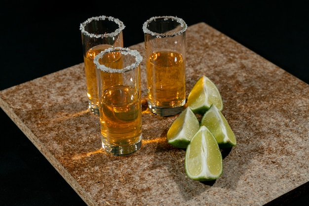 Goldener tequila mit zitrone und salz. getränke, schnaps