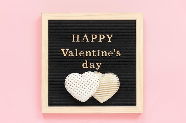 Goldener text glücklicher valentinstag und zwei dekorationstextilherzen auf brett der schwarzen schrift, zentrale zusammensetzung auf rosa hintergrund