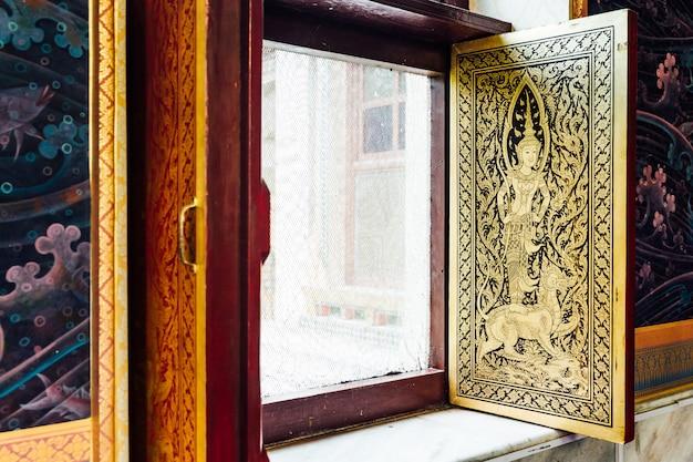 Goldener thailändischer engel verziert auf fenster innerhalb des thailändischen klosters bei bodh gaya, bihar, indien.