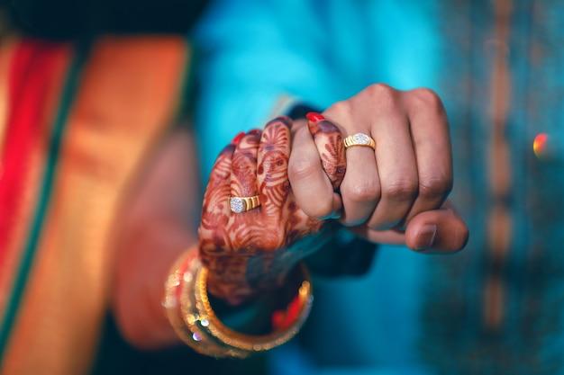 Goldener verlobungsring in der paarhand