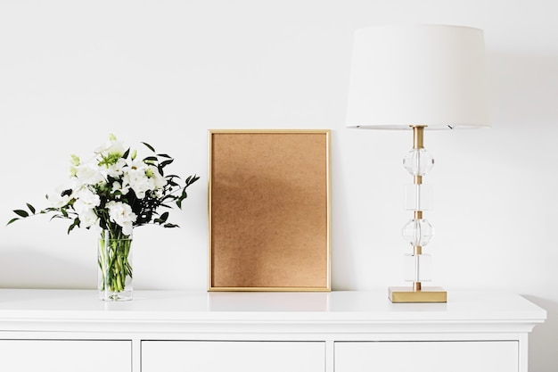 Goldener vertikaler rahmen und strauß frischer blumen auf weißen möbeln, luxuriöse wohnkultur und design für mockup-kreationen