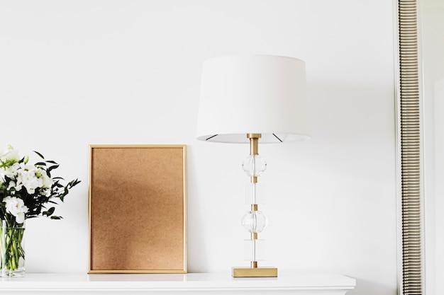 Goldener vertikaler rahmen und strauß frischer blumen auf weißen möbeln, luxus-wohnkultur und design für ...