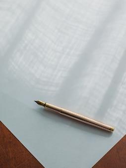 Goldener vintage tintenstift auf ein stück weißes papier gelegt