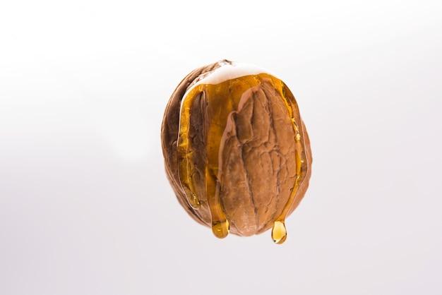 Goldener walnussöltropfen tropft von ganzen akrod- oder akhrot-trockenfrüchten, die isoliert in der luft fliegen
