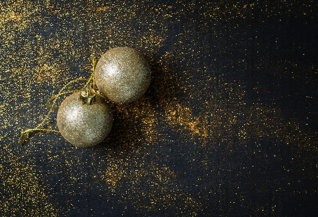 Goldener weihnachtsball auf funkeln und schwarzem hölzernem tabellenhintergrund mit schwarzem kopienraum.
