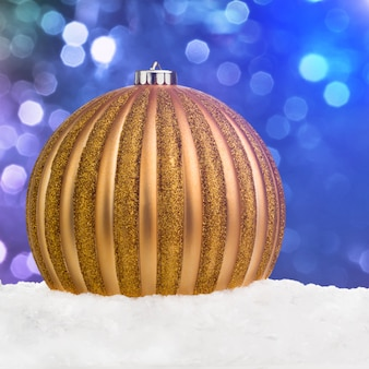 Goldener weihnachtsball auf schnee über blauem defocused hintergrundesprit