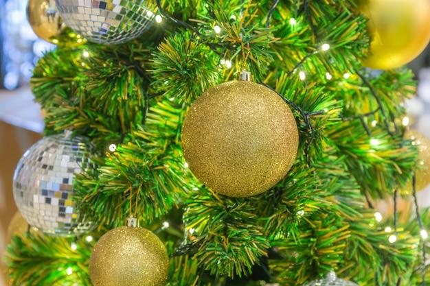 Goldener weihnachtsball, der am weihnachtsbaum mit grünem bokeh in der nachtzeit hängt