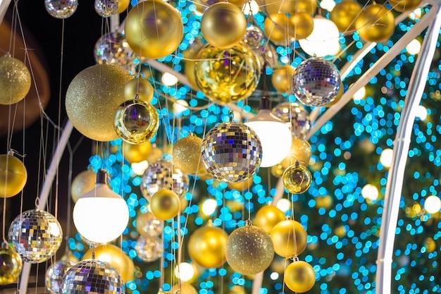 Goldener weihnachtsball, der am weihnachtsbaum mit hellblauem bokeh in der nachtzeit hängt