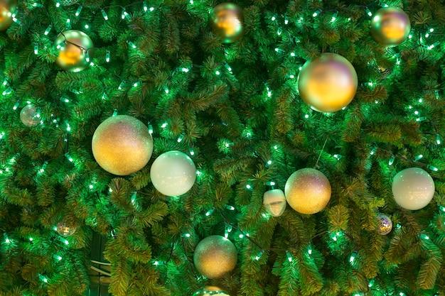 Goldener weihnachtsball, der am weihnachtsbaum mit licht in der nachtzeit hängt