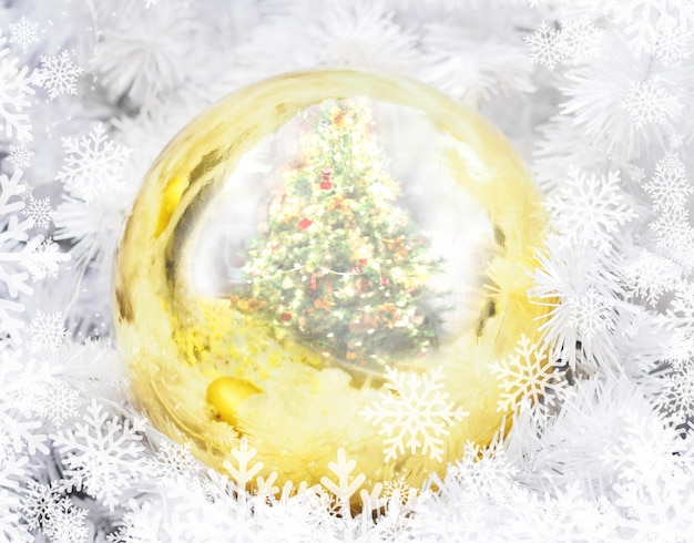 Goldener weihnachtsball mit kiefernreflexions- und schneeflockenmuster.