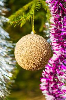 Goldener weihnachtsball und glänzender lametta, der am ast des baumes hängt. nahaufnahme der weihnachtsfeiertagszusammensetzung für ein frohes neues jahr
