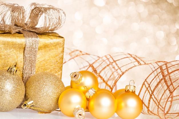 Goldener weihnachtsbaumschmuck gegen lichterhintergrund
