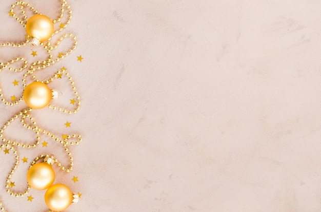 Goldener weihnachtshintergrund. perlen mit dekorativen kugeln und sternen.