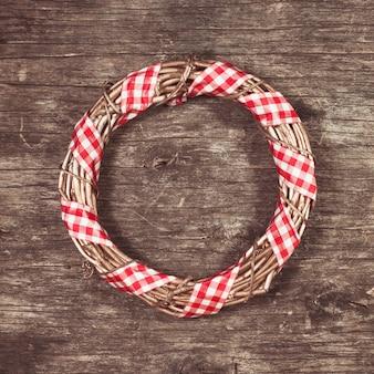 Goldener weihnachtskranz mit rotem ginghamband