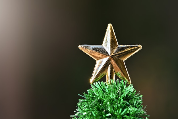 Goldener weihnachtssternball auf verzierungskiefern-weihnachtswipfelnahaufnahme auf dunklem hintergrund