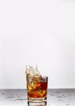 Goldener whisky im glas mit eiswürfeln auf dem tisch, draufsicht. platz für text