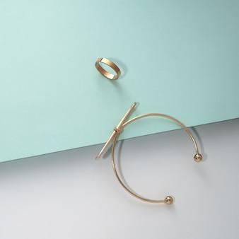 Goldenes armband und ring auf blauem und weißem hintergrund