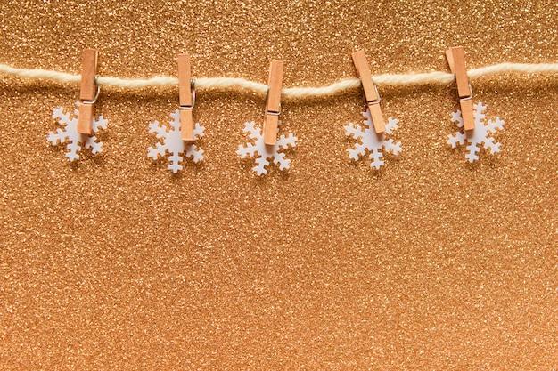 Goldenes backgound mit festgesteckten weißen schneeflocken