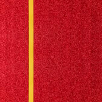 Goldenes band des schönen glänzenden satins auf buntem rotem funkelnpapier oder geschenkboxhintergrund