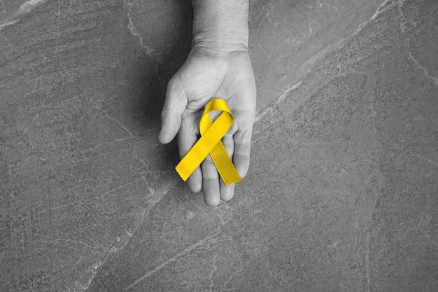 Goldenes band kindheitssymbol des kampfes gegen krebs bei kindern in händen auf grauer wand. konzept zur unterstützung von patienten mit sarkom und blasenkrebs.